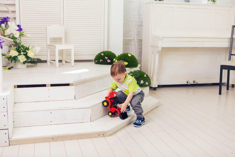 O rapaz pequeno está jogando com carro do brinquedo em casa fotografia de stock