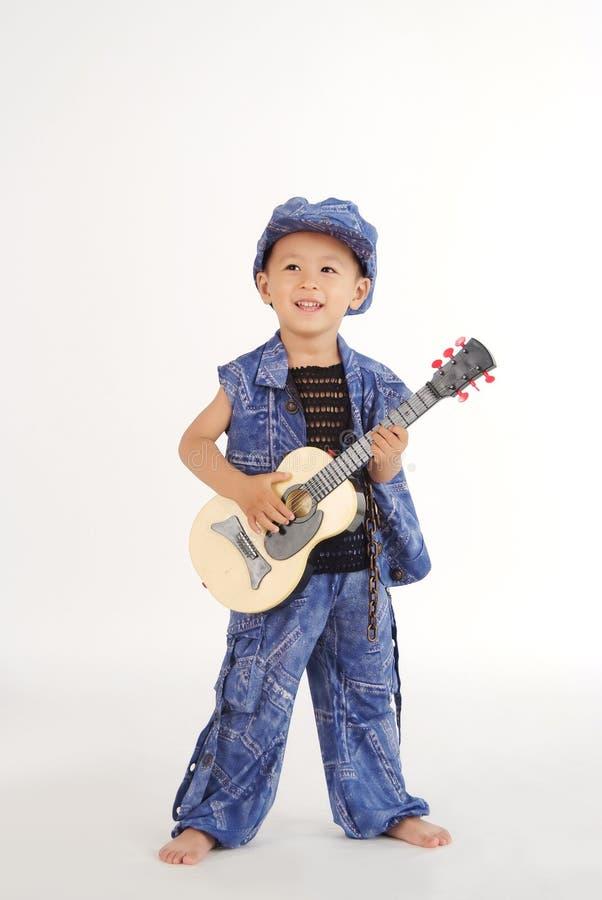 O rapaz pequeno está jogando a guitarra fotografia de stock royalty free