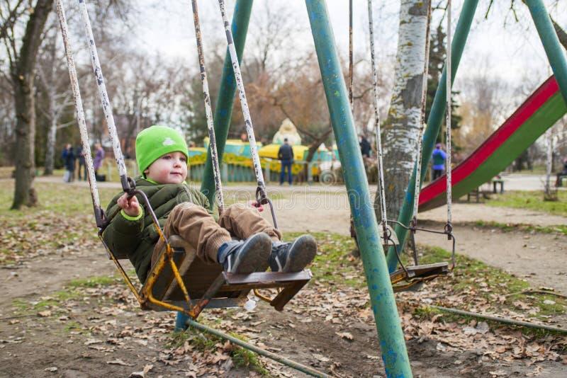 O rapaz pequeno está montando em um balanço no parque foto de stock
