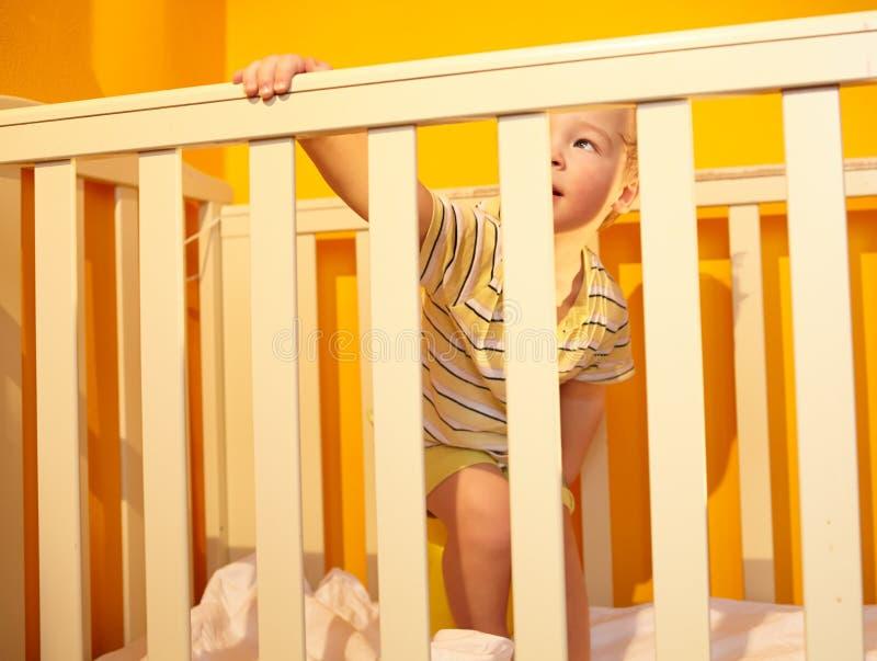 O rapaz pequeno está na cama fotos de stock