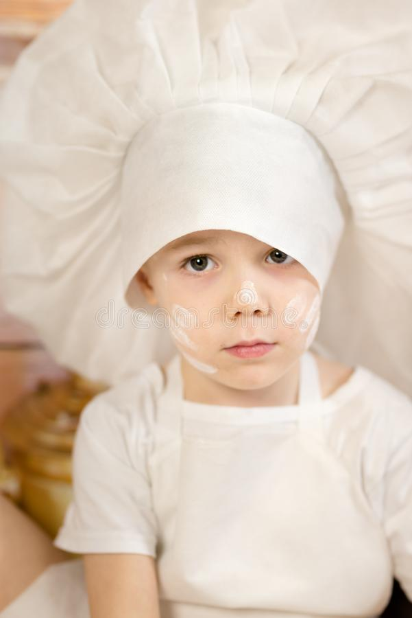 O rapaz pequeno está preparando o bolo e as panquecas Vestido como uma massa da criança do cozinheiro chefe prepara o alimento foto de stock