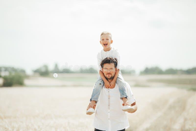 O rapaz pequeno está sentando-se em seus ombros a do pai no campo de trigo fotografia de stock