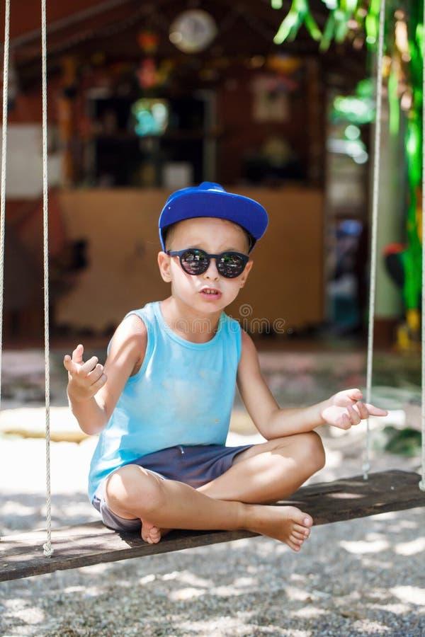 O rapaz pequeno está sentando-se em um balanço imagens de stock
