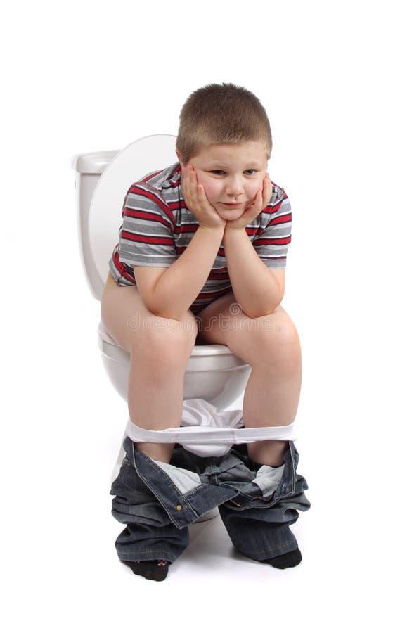 O rapaz pequeno está sentando-se no toalete imagem de stock