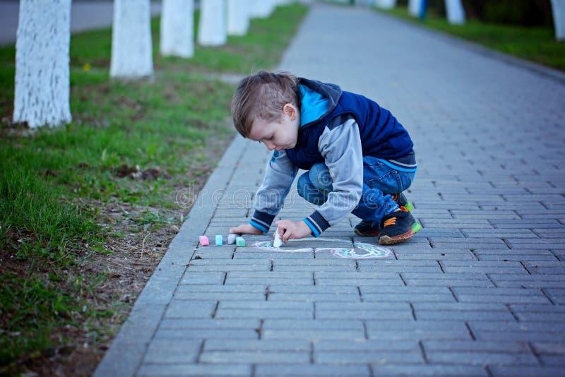 O rapaz pequeno está tirando no asfalto no parque da mola fotos de stock royalty free