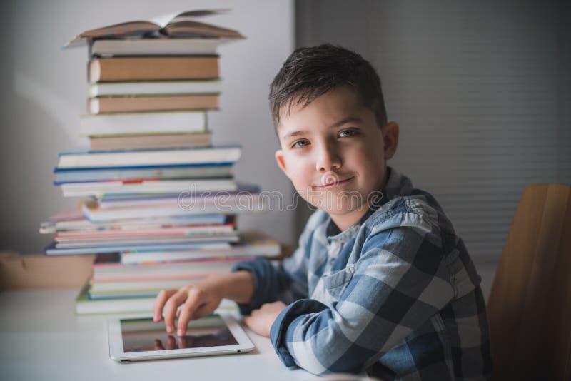 O rapaz pequeno está usando uma tabuleta imagem de stock