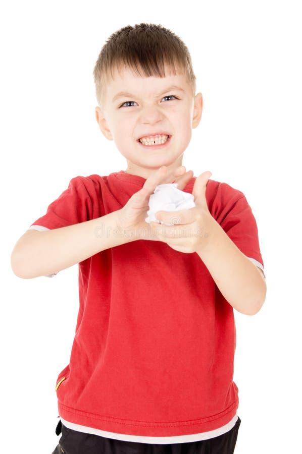 O rapaz pequeno estava irritado e amarrota a folha de papel imagem de stock royalty free