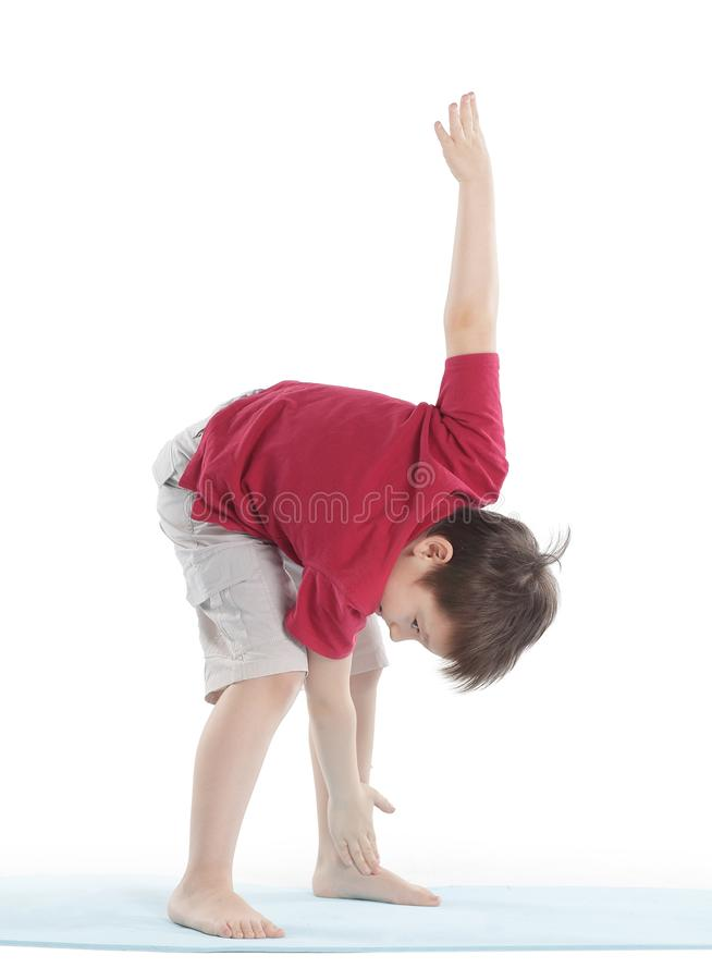 O rapaz pequeno executa um exercício para esticar os músculos Isolado no branco fotos de stock royalty free