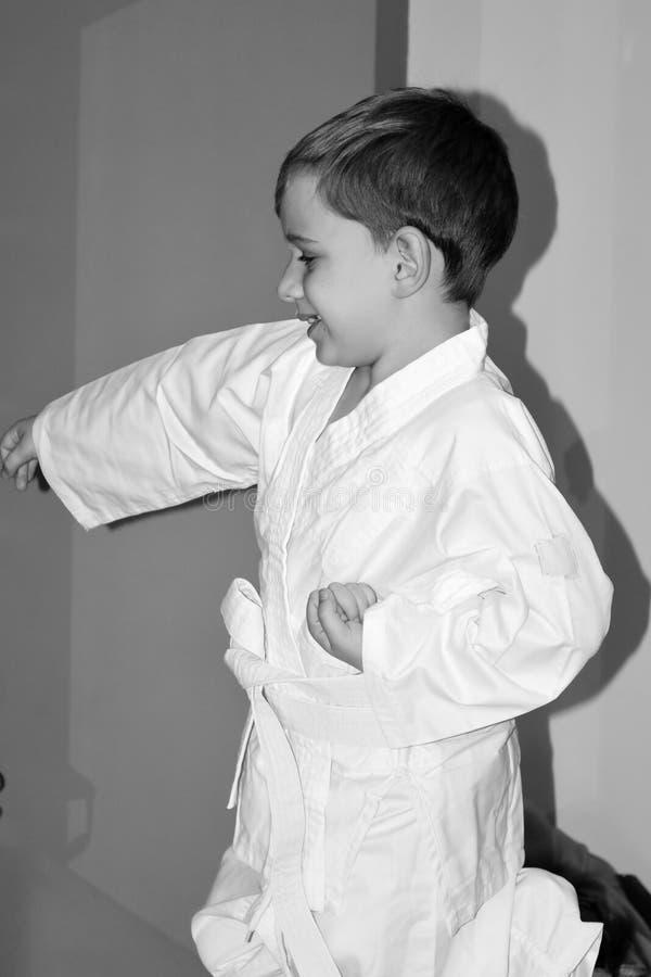 O rapaz pequeno faz exercícios do karaté foto de stock