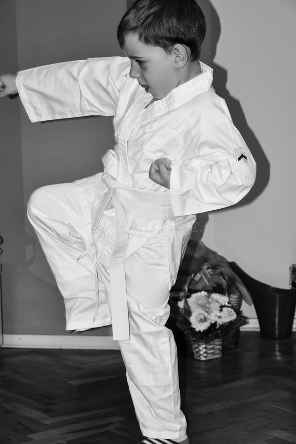O rapaz pequeno faz exercícios do karaté fotos de stock