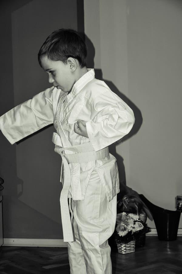 O rapaz pequeno faz exercícios do karaté imagens de stock