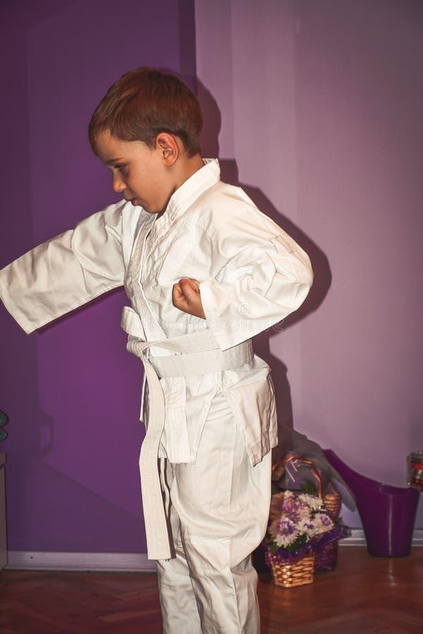 O rapaz pequeno faz exercícios do karaté imagem de stock