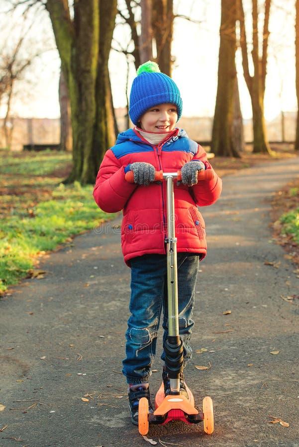 O rapaz pequeno feliz aprende montar o 'trotinette' no parque do outono As crianças ostentam o ar livre Forma das crianças do out imagens de stock royalty free