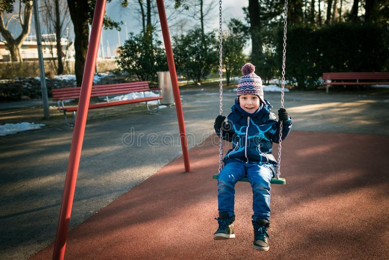 O rapaz pequeno feliz no balanço no dia de inverno bonito tem o divertimento e faz as caras fotografia de stock