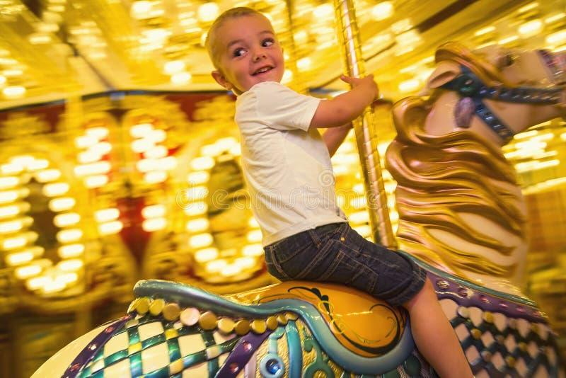 O rapaz pequeno feliz que monta um alegre vai carrossel do círculo com luzes brilhantes fotografia de stock