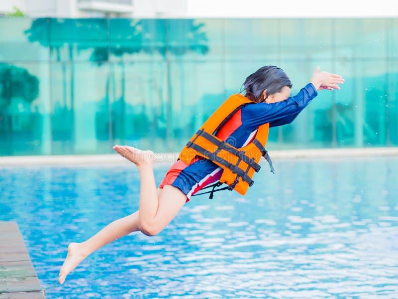 O rapaz pequeno feliz que veste o revestimento de vida alaranjado tem o divertimento e aprecia-o saltar na piscina imagens de stock