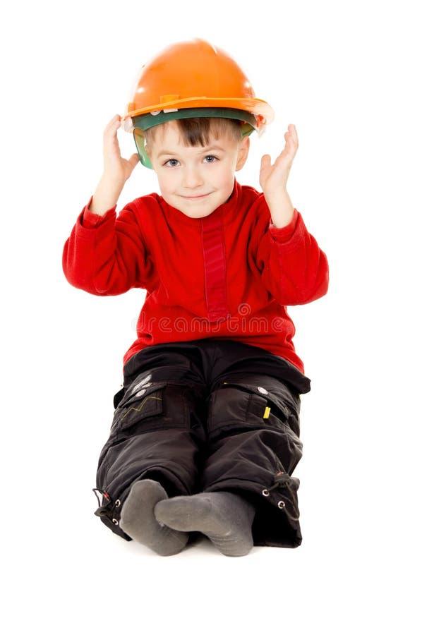 O rapaz pequeno feliz senta-se com um capacete foto de stock