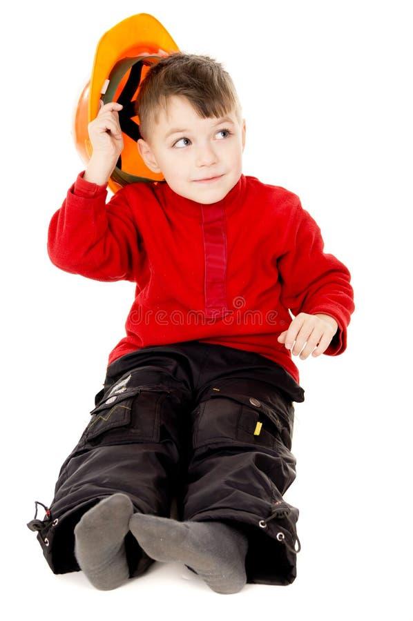 O rapaz pequeno feliz senta-se com um capacete imagem de stock royalty free