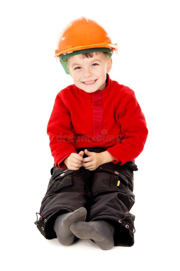 O rapaz pequeno feliz senta-se com um capacete imagens de stock royalty free