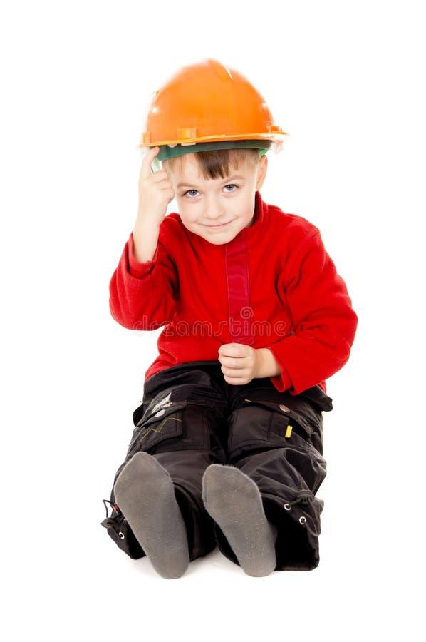 O rapaz pequeno feliz senta-se com um capacete fotografia de stock royalty free