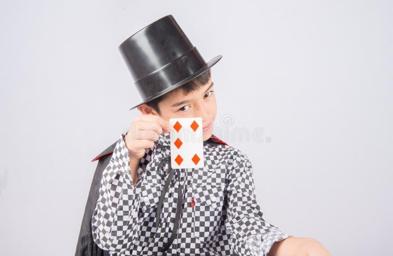 O rapaz pequeno finge como um desempenho do mágico com divertimento foto de stock royalty free