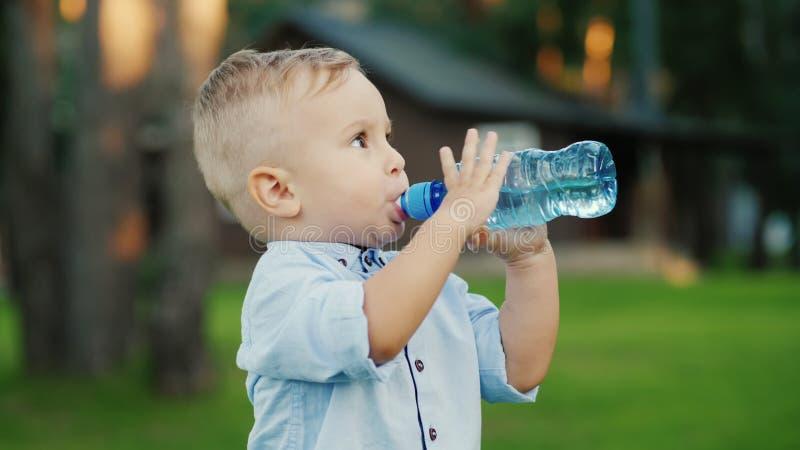 O rapaz pequeno foi água potável da garrafa por 1 ano Estar no quintal de sua casa imagens de stock