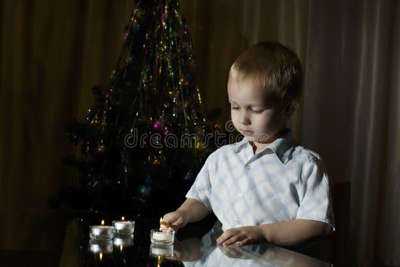 O rapaz pequeno ilumina velas em um fundo do abeto do ` s do ano novo imagem de stock