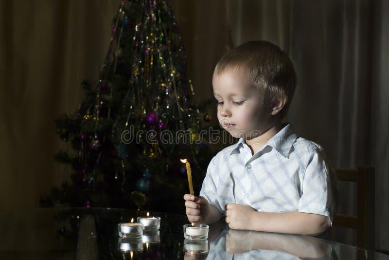 O rapaz pequeno ilumina velas em um fundo do abeto do ` s do ano novo fotografia de stock