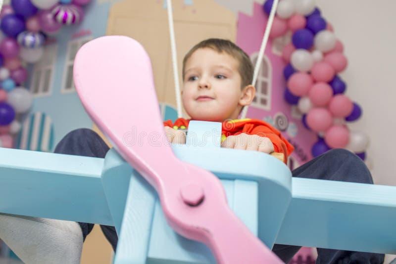 O rapaz pequeno imagina-se como um piloto do avião na sala de crianças imagens de stock royalty free