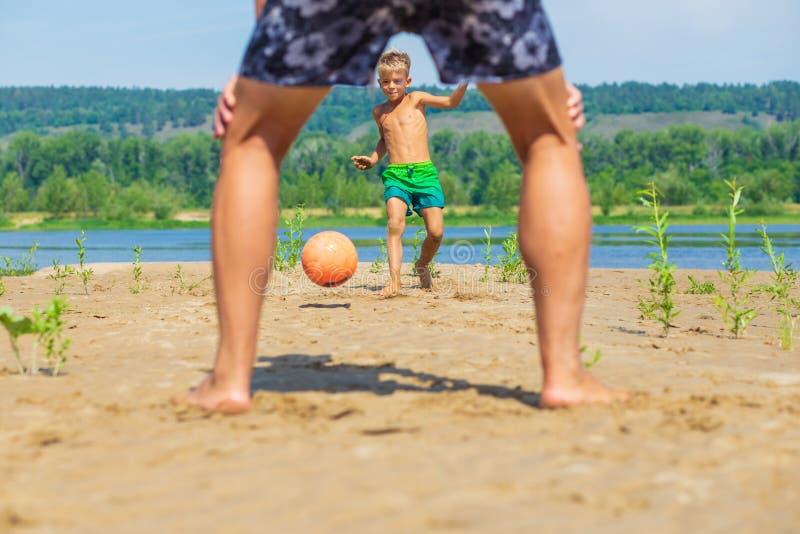 O rapaz pequeno joga a bola na praia fotos de stock