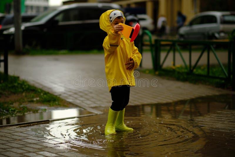 O rapaz pequeno joga com um barco plástico em uma poça em um dia chuvoso do outono imagens de stock