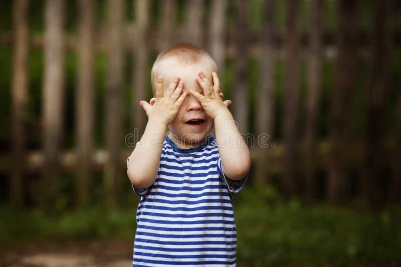 O rapaz pequeno joga o esconde-esconde fotos de stock