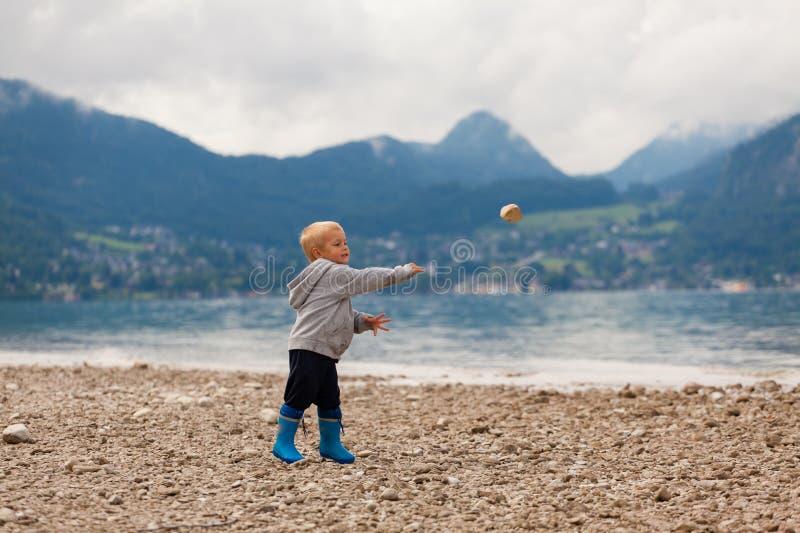 O rapaz pequeno joga pedras na água imagem de stock
