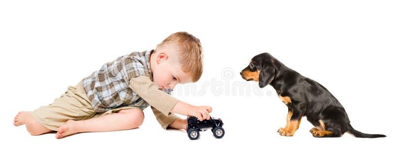 O rapaz pequeno joga um carro do brinquedo com seu cachorrinho fotos de stock