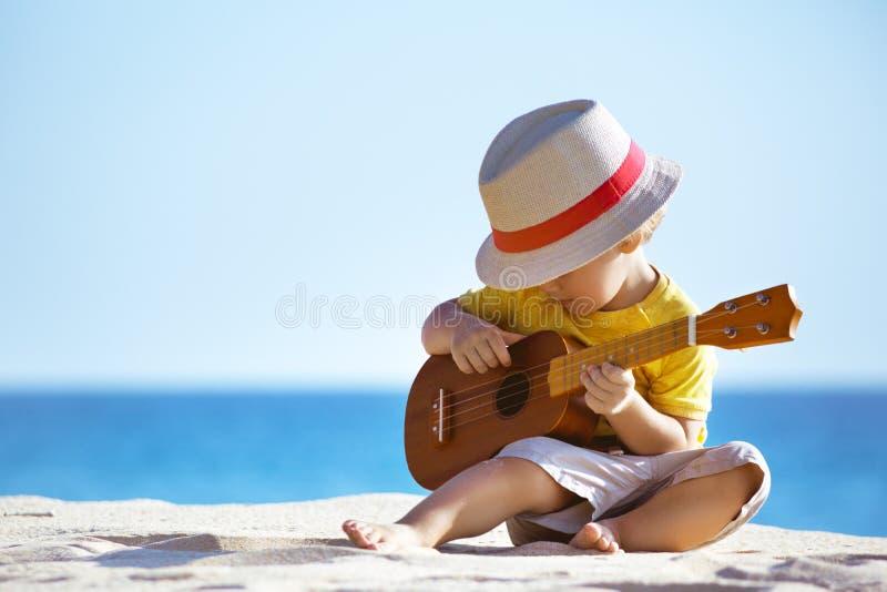 O rapaz pequeno joga a uquelele da guitarra na praia do mar fotografia de stock royalty free