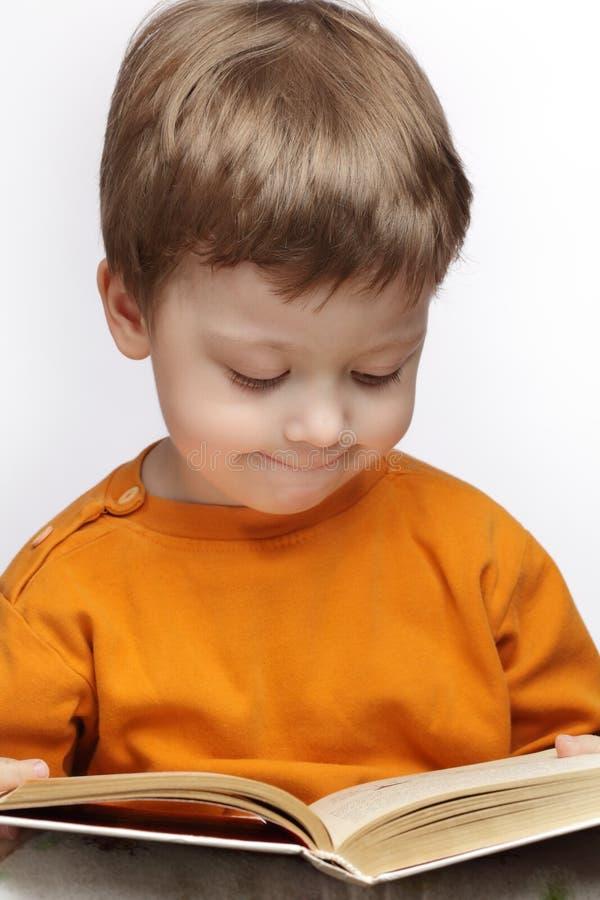 O rapaz pequeno leu o livro fotografia de stock royalty free