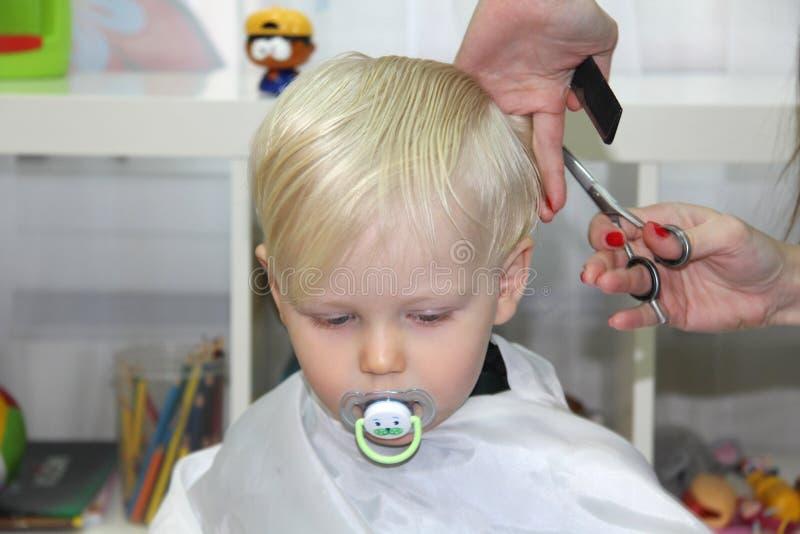 O rapaz pequeno louro cortou seu cabelo em um cabeleireiro das crianças fotos de stock