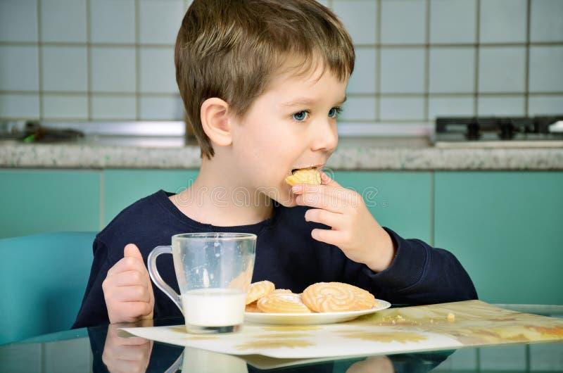 O rapaz pequeno morde as cookies, sentando-se na tabela de jantar horizont fotos de stock
