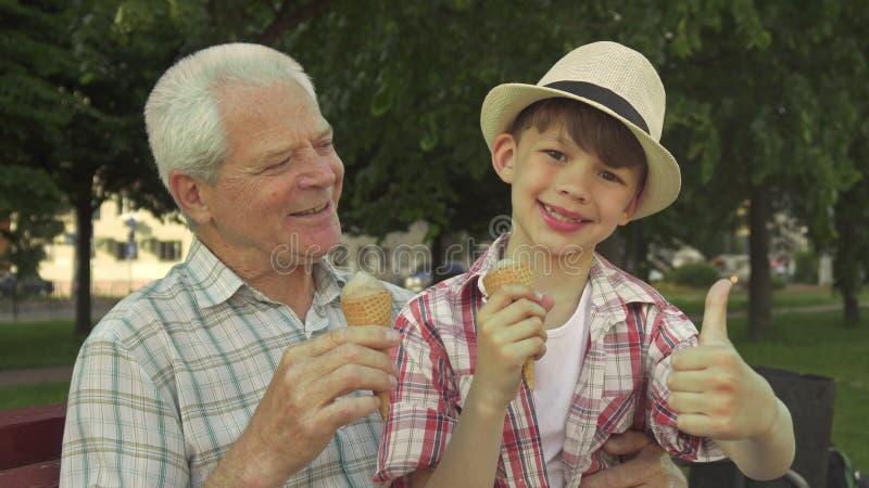 O rapaz pequeno mostra seu polegar acima perto de seu vovô fotos de stock royalty free