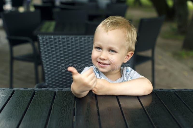 O rapaz pequeno mostra um agradável foto de stock royalty free