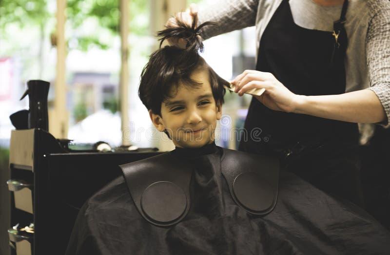 O rapaz pequeno no cabelo da barbearia cortou profissional fotografia de stock royalty free