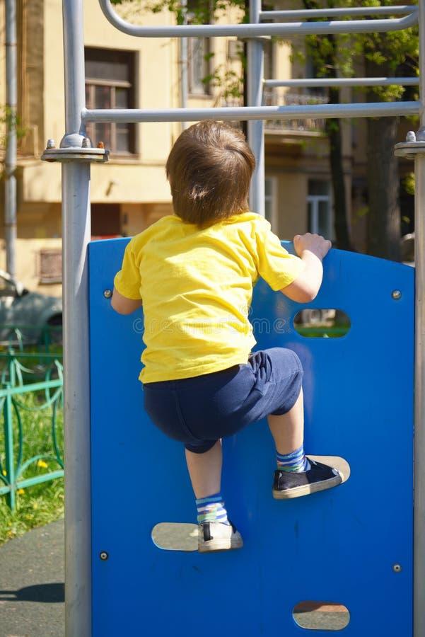 O rapaz pequeno no campo de jogos joga esportes Motivação da aptidão foto de stock royalty free