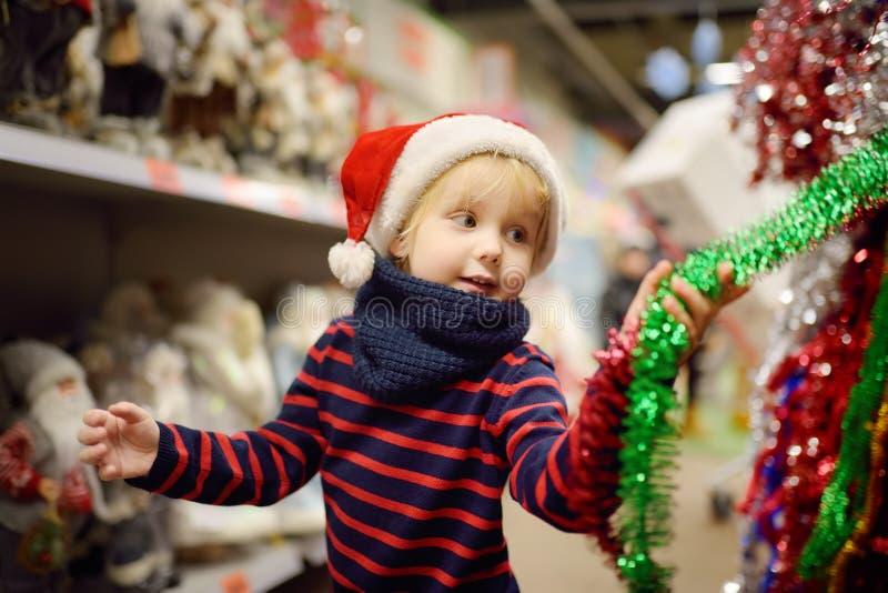 O rapaz pequeno no chapéu de Santa escolhe decorações do Natal no mercado Decoração tradicional do xmas foto de stock
