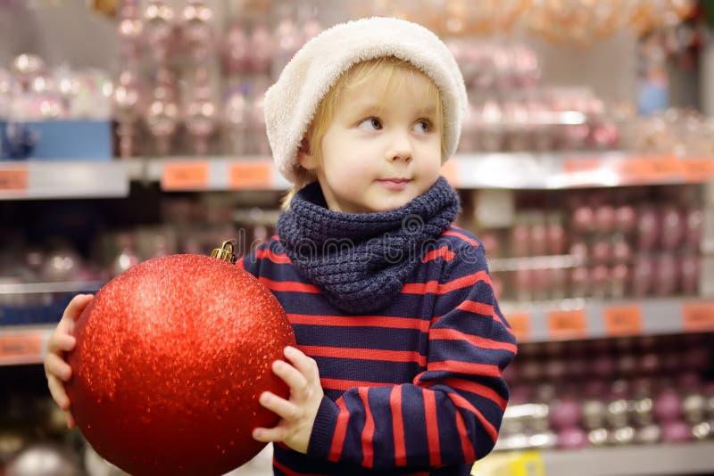 O rapaz pequeno no chapéu de Santa escolhe decorações do Natal no mercado Decoração tradicional do xmas fotos de stock royalty free