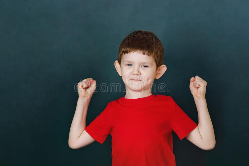 O rapaz pequeno no t-shirt vermelho que mostra seu bíceps da mão muscles imagem de stock