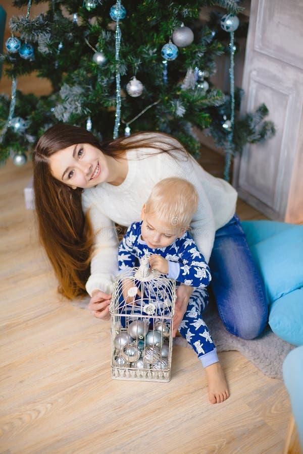 O rapaz pequeno nos pijamas senta-se e sorri-se com sua irmã perto da árvore de Natal foto de stock