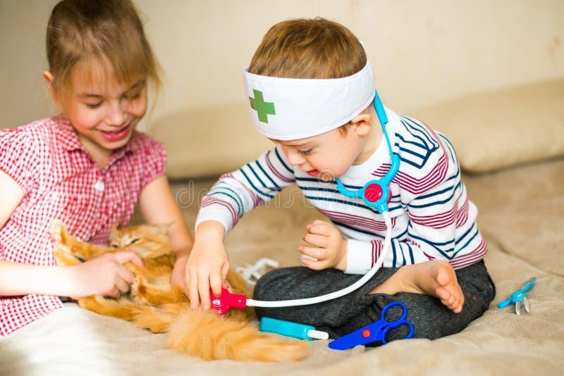 O rapaz pequeno nos vidros com alvorecer da síndrome e a menina do louro jogam com brinquedos e gato do gengibre fotos de stock