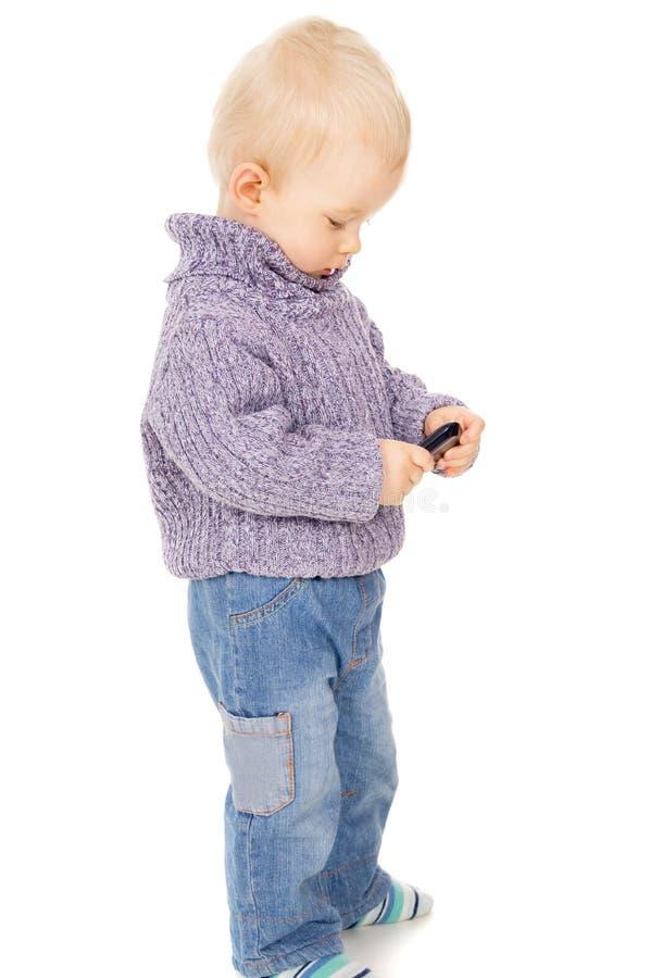 O rapaz pequeno olha no telemóvel foto de stock royalty free