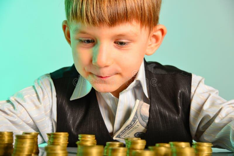 O rapaz pequeno olha suas economias do dinheiro com prazer O conceito ávido e vicioso da economia do negócio das crianças foto de stock royalty free