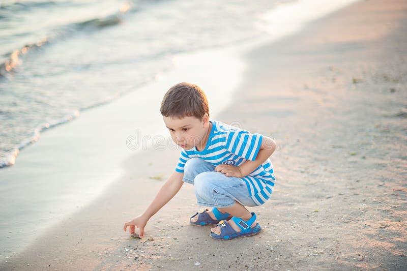 O rapaz pequeno pelo mar joga pedras na água Por do sol Infância feliz fotos de stock